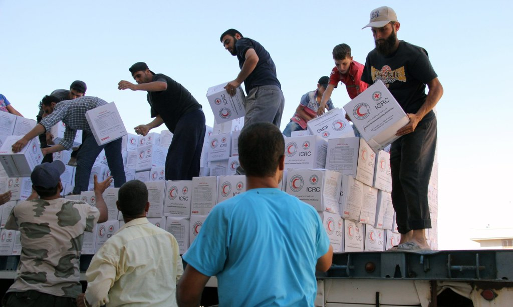 Syrians unload boxes after a 48-truck convoy from the ICRC, SARC and UN entered the Syrian rebel-held town of Talbiseh. Photograph: Mahmoud Taha/AFP