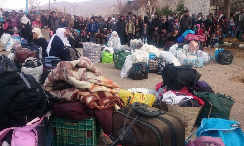 Syrians wait for the arrival of an aid convoy in the besieged town of Madaya. Photograph: Marwan Ibrahim/AFP/Getty Images