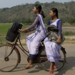 Indian girls go to a school on a bicycle at Roja Mayong village about 40 kilometers (25 miles) east of Gauhati, India