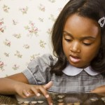 Girl counting  change from piggy bank