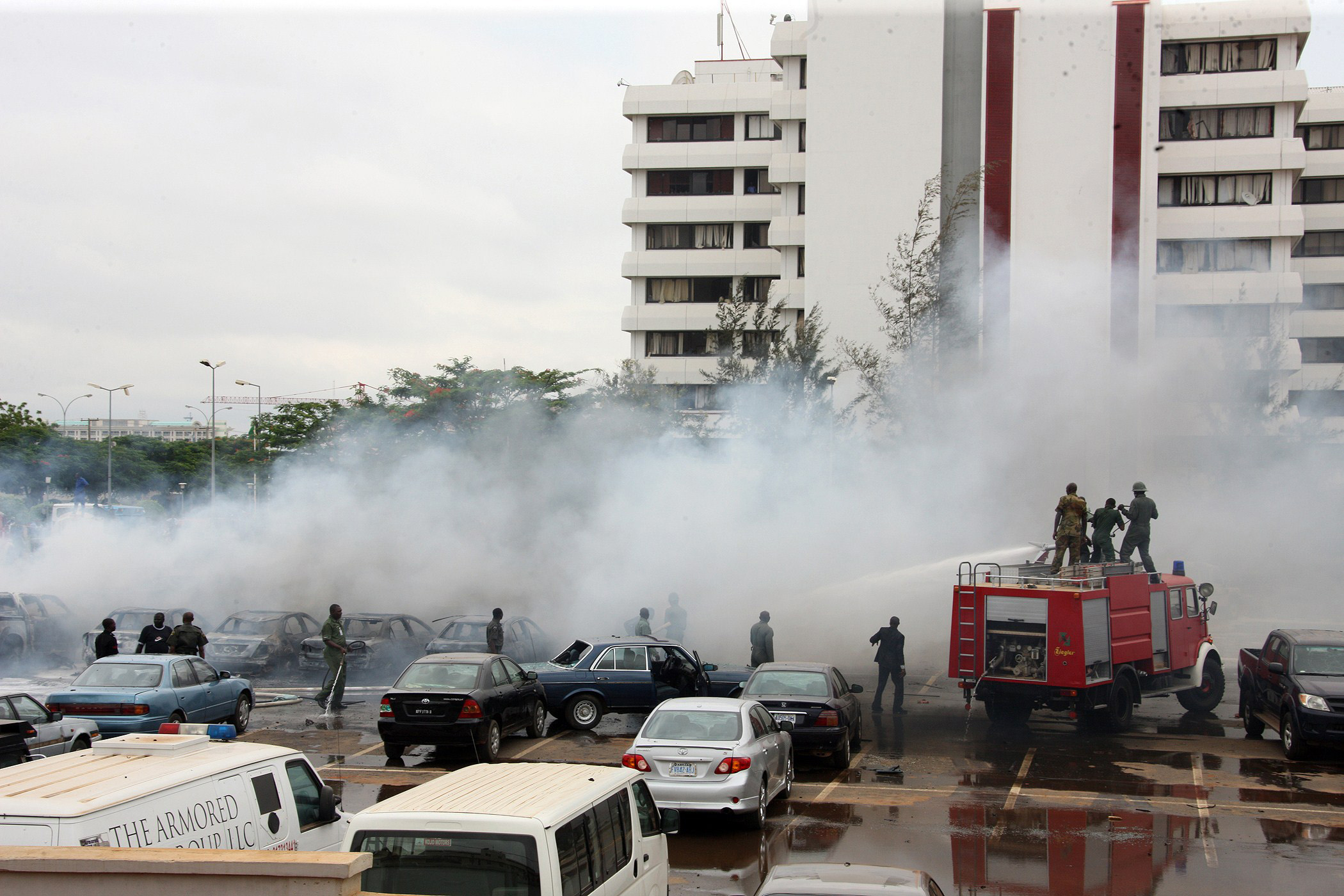"Firefighters try to extinguish a fire after a bomb blast at the parking lot of police headquaters in Abuja on June 16, 2011. The bomb killed two people and damaged several vehicles. Nigerian police suspect the radical Islamic sect Boko to be behind the ""suicide"" bombing. The Islamist Boko Haram sect on June 15, 2011 threatened ""fiercer"" attacks and said it would not enter into talks with the government, which it had earlier proposed. AFP PHOTO/ SUNDAY AGHAEZE (Photo credit should read Sunday Aghaeze/AFP/Getty Images)"
