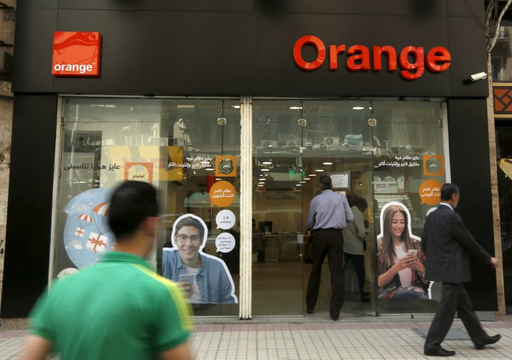 People walk past a new shop of French telecom operator Orange, which was previously known as Mobinil, in Cairo, Egypt, April 6, 2016. REUTERS/Amr Abdallah Dalsh