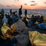 A group of rescued people on the deck of an Italian naval vessel as the sun sets in the Mediterranean. ©UNHCR/A. D'Amato