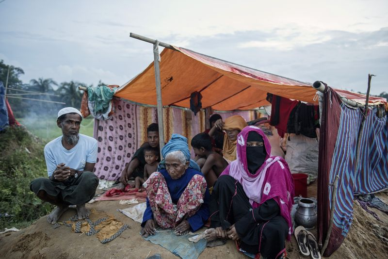 A Rohingya family sits under a makeshift tent at a refugee camp in Cox's Bazar, Bangladesh. Photographer: Ismail Ferdous/Bloomberg