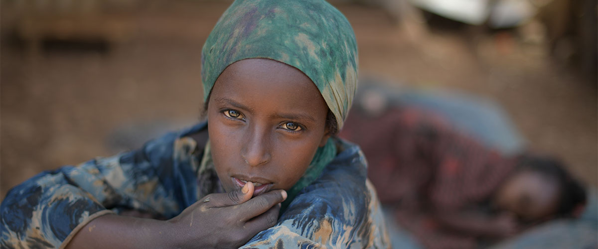 A young girl sits in the shade, while her sister sleeps behind her, at an IDP camp in Baidoa for victims of a drought currently affecting Somalia. UN Photo/Tobin Jones