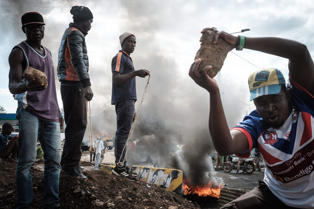 Opposition supporters hold up bricks as they block streets and burn tires during a protest in Kisumu, Kenya, on October 11, 2017. Supporters of Kenya's opposition leader Raila Odinga took to the streets as poll officials mull their next move after his withdrawal from a presidential election plunged the country into uncharted waters. / AFP PHOTO / YASUYOSHI CHIBA        (Photo credit should read YASUYOSHI CHIBA/AFP/Getty Images)