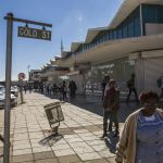 Pedestrians walk by closed-down retail outlets on Gold Street in Carletonville. Photographer: Guillem Sartorio/Bloomberg