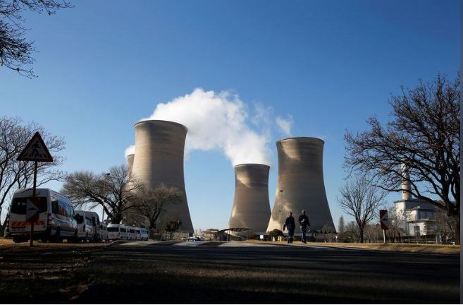 Workers are seen near cooling towers of the Hendrina power station, located south of Middelburg, South Africa, July 13, 2018. Picture taken July 13, 2018. REUTERS/Siphiwe Sibeko