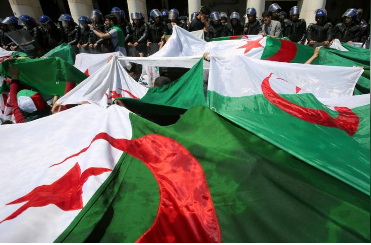 Police members stand guard as students carry national flags during an anti-government protest in Algiers, Algeria May 14, 2019. REUTERS/Ramzi Boudina/File Photo