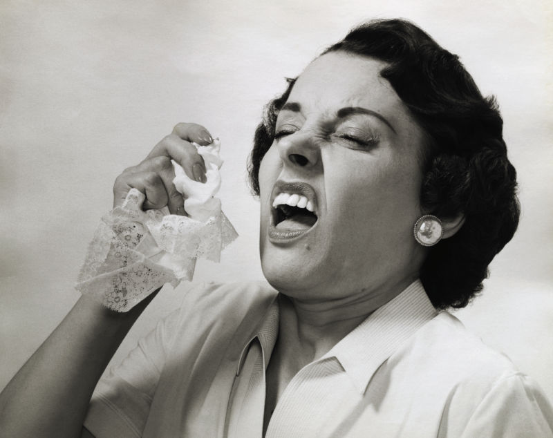 (Original Caption) Picture shows a woman about to sneeze holding a handkerchief in her hand. Undated photo.
