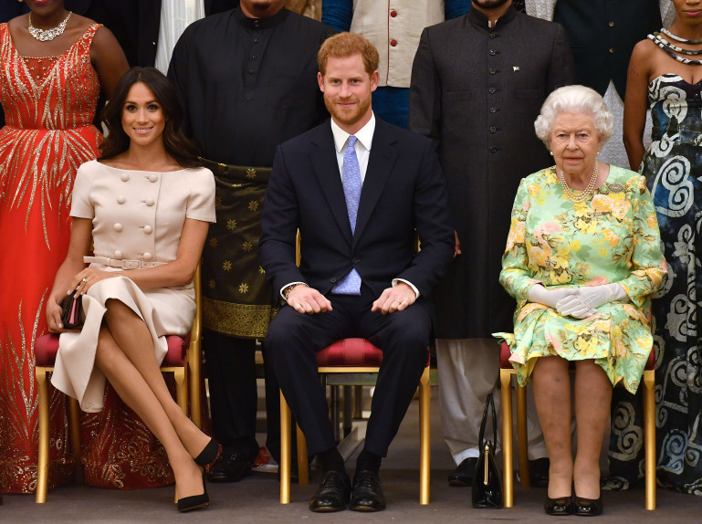 (L-R) Meghan, Duchess of Sussex, Britain's Prince Harry, Duke of Sussex and Britain's Queen Elizabeth II pose for a photo. Photo by John Stillwell / POOL / AFP/Getty Images