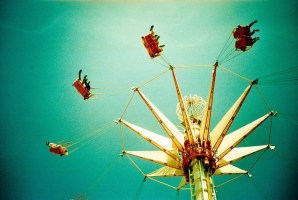 image of merry-go-round viewed from below with people looking like they are flying legs outstretched