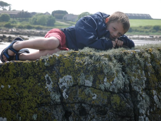 young boy lying on a wall by a river