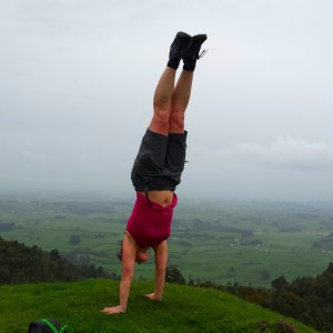 woman doing a handstand on the top of a hill