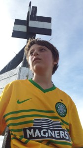 teenage boy wearing a yellow and green football shirt sitting under a Trig point in New Zealand