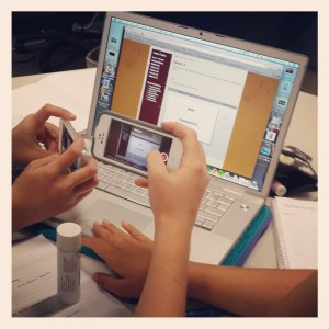 hands holding smartphones to take a video of a pronunciation activity on a laptop screen