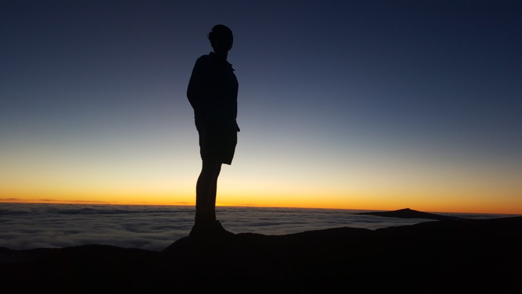boy standing on a rock above the clouds at sunset