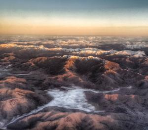 Morning light shin8ng on tops of mountains. View from the air. Cloud in the valleys.