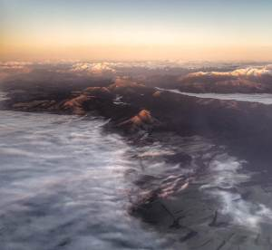 On the right mountains, dark seen from above. To the left the cloud covers the ground.