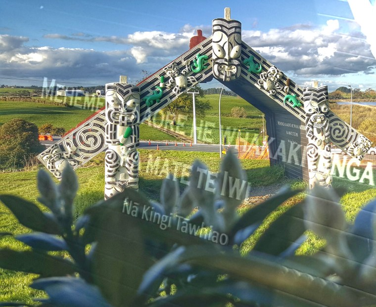 a collage of two photos. One of the carved entrance way to a Pā sute, the other are the words inscribed on the inside of the gateway.