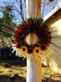 Wreath with lavender sprigs, chile pequin, local juniper, homegrown Indian corn, sand dried zinnias and wild sunflowers on a corn husk wreath base.