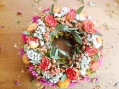 Snake weed wreath base with statice, strawflowers, culinary sage, roses and wild acorns found in Penasco.