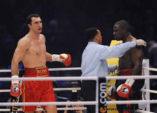 Referee Tony Weekf of the United States intervenes to save Rahman from further punishment  during the  bout in the seventh round ...............