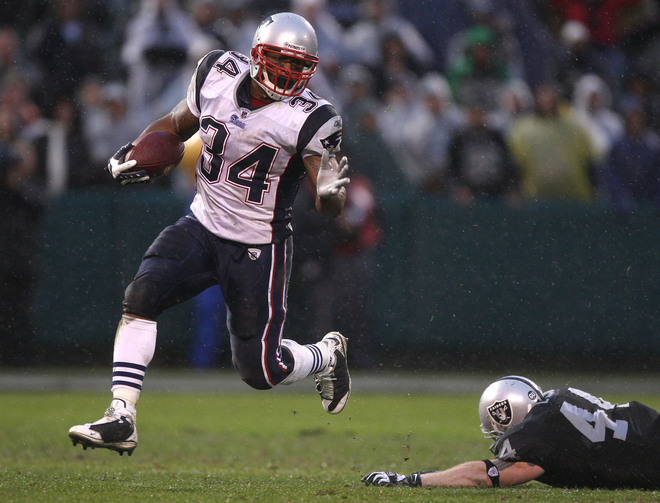 Patriots' running back Sammy Morris(34) evades the attempted tackle by  the Raiders' Luke Lawton(44)