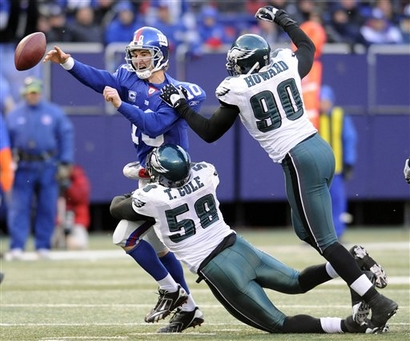 Manning throws an incomplete pass whilst being tackled by the  Eagles' Trent Cole  and  Darren Howard in a regular season  game won by the Eagles  20-14....................