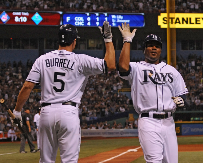 Rays'  players  Pat  Burrell  and  Carl  Crawford  celebrate a  run  being  scored  .