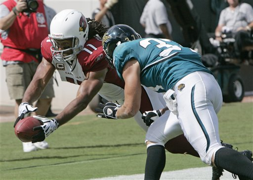 Cardinals'  wide   receiver  Larry  Fitzgerald   gets  into the  endzone  as   Jags'  safety    Sean  Considine  is   unable   to  derail   Fitzgerald  in  his   effort  .        picture  appears  courtesy  of ap/ photo/ Phil  Coale  .................