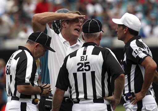 Jacksonville  Jaguars' coach   Jack  Del  Rio  (center)  contests    a call  by officials   Greg  Gautreaux (80),  Bob Waggoner  (25)  and   Gene Steratore (14)  in  the  first   half   of  the   game  played   between the   Jaguars and  Arizona  Cardinals  .    picture    appears  courtesy  of  ap/photo/  Phil   Coale   .........................