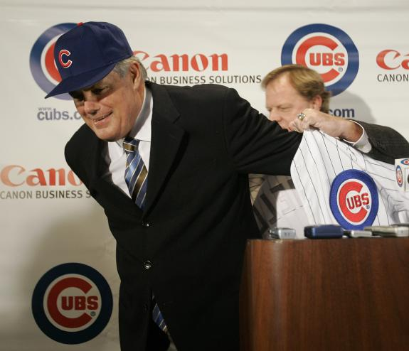 Lou  Piniella  is  formally introduced  as   the  Chicago  Cubs'  manager.   Assisting  him  in  putting  on the  team  jersey  is   the  GM  Jim Hendry.     Piniella  took  over the   position  from the  fired   Dusty  Baker   .  He  assumed those  responsibilities  on   October of   2006.  He  signed a  three  year  conract  for   $10m    with a  1 year   option  extra as  an  incentive.   picture  appears  courtesy  of   upi/photo/  Brian  Kersey  .....................