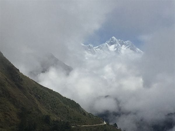 A view of Himalayan peaks cresting above the clouds on the road to the Tengboche monastery