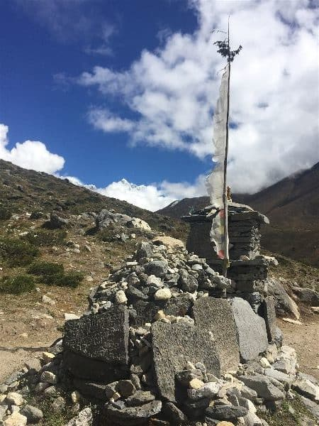 A makeshift religious site, with tablets inscribed with scriptures and covered with tattered and worn prayer flags