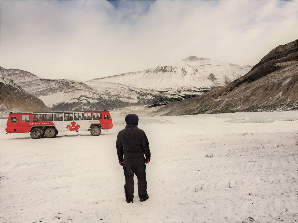 A Brewster Canada employee makes sure that no-one walks where they shouldn't on the Athabasca Glacier, whilst another Ice Explorer Bus arrives