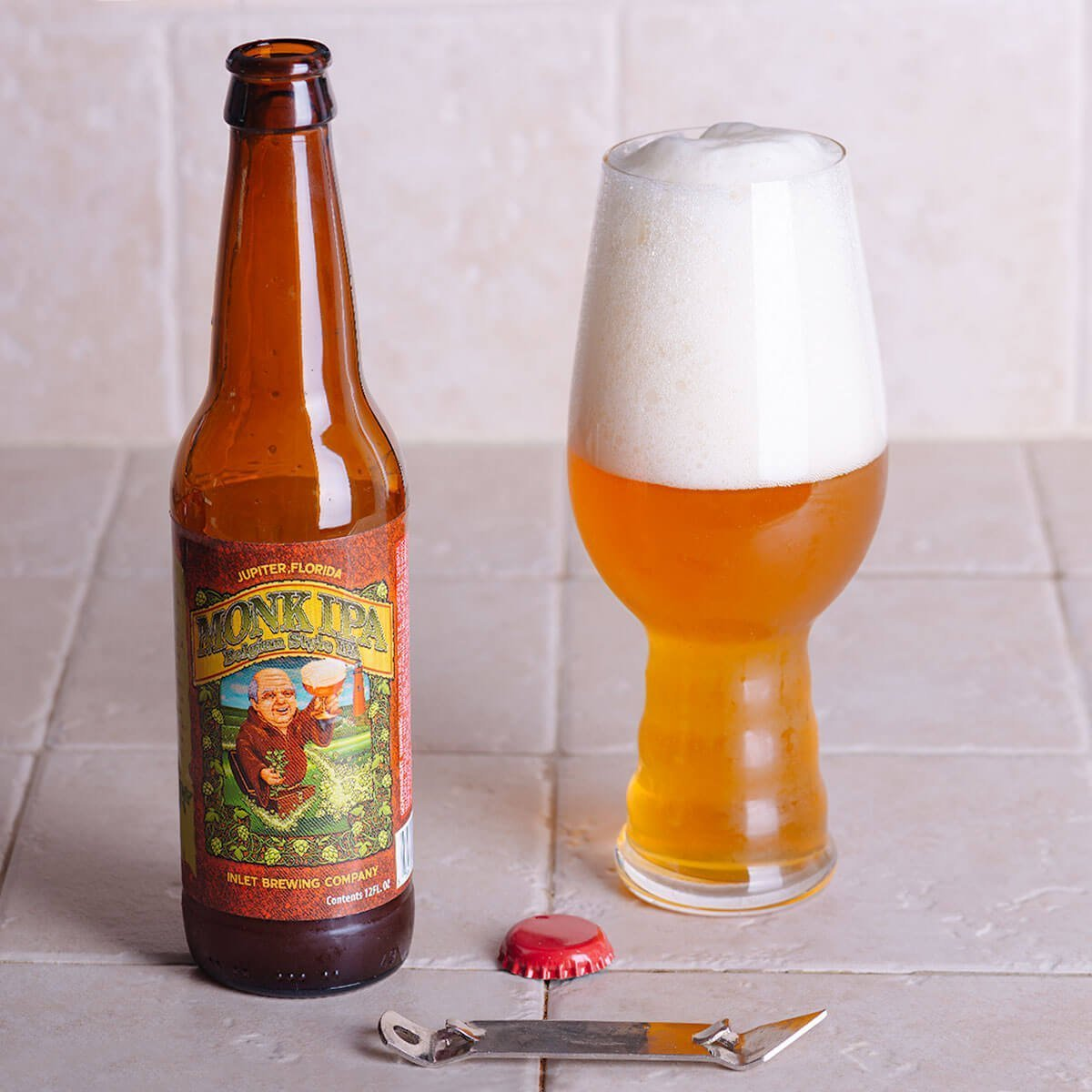 Monk IPA is a Belgian-style IPA by Inlet Brewing Company whose hop-forward character is complemented by yeast, tropical fruit, and bready malt.