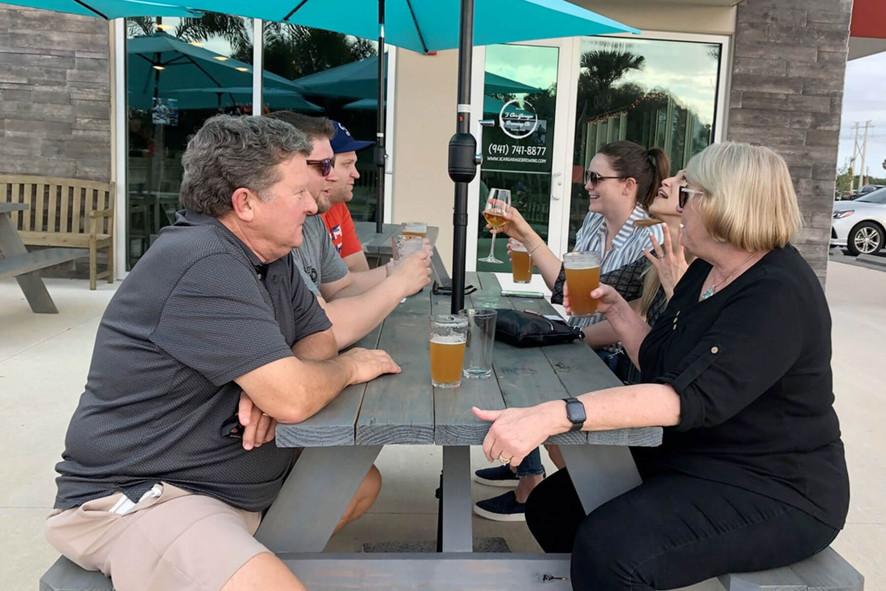 Beer drinkers sit at table on the patio outside 3 Car Garage Brewing in Bradenton, Florida