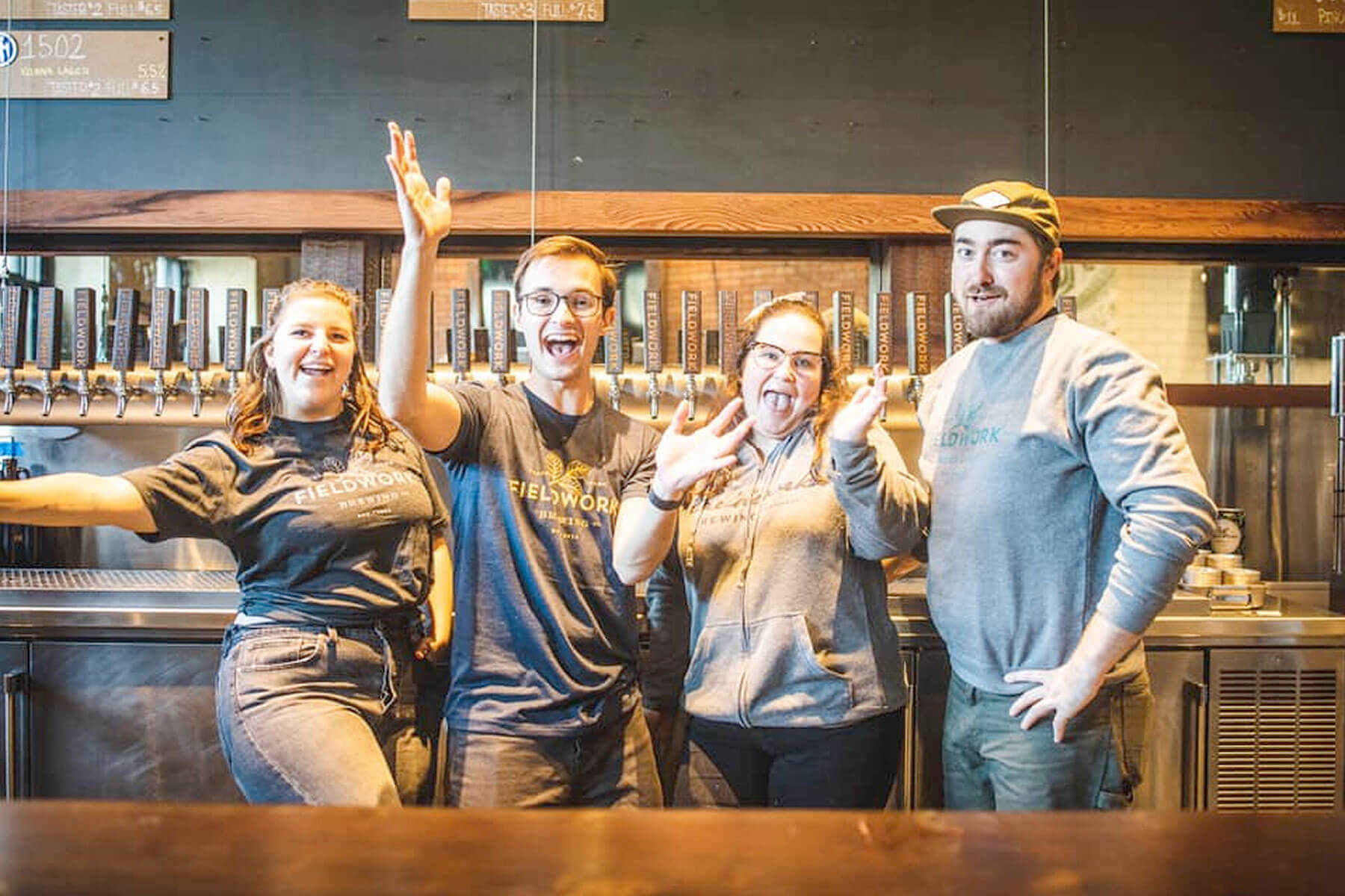 Bartenders show their joy in the taproom at Fieldwork Brewing Company in Corte Madera, California