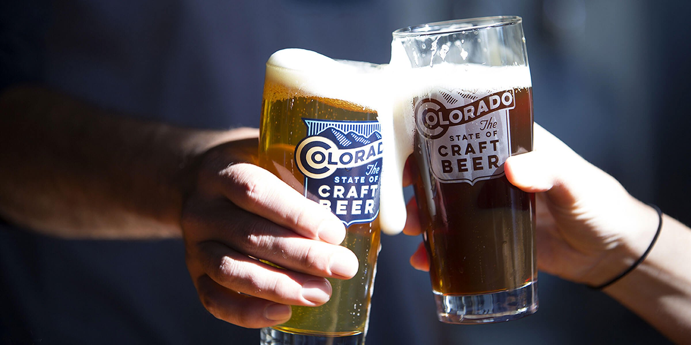 """Two people toasting with beers in """"The State of Craft Beer"""" branded Willi Becher pint glasses from the Colorado Brewers Guild"""