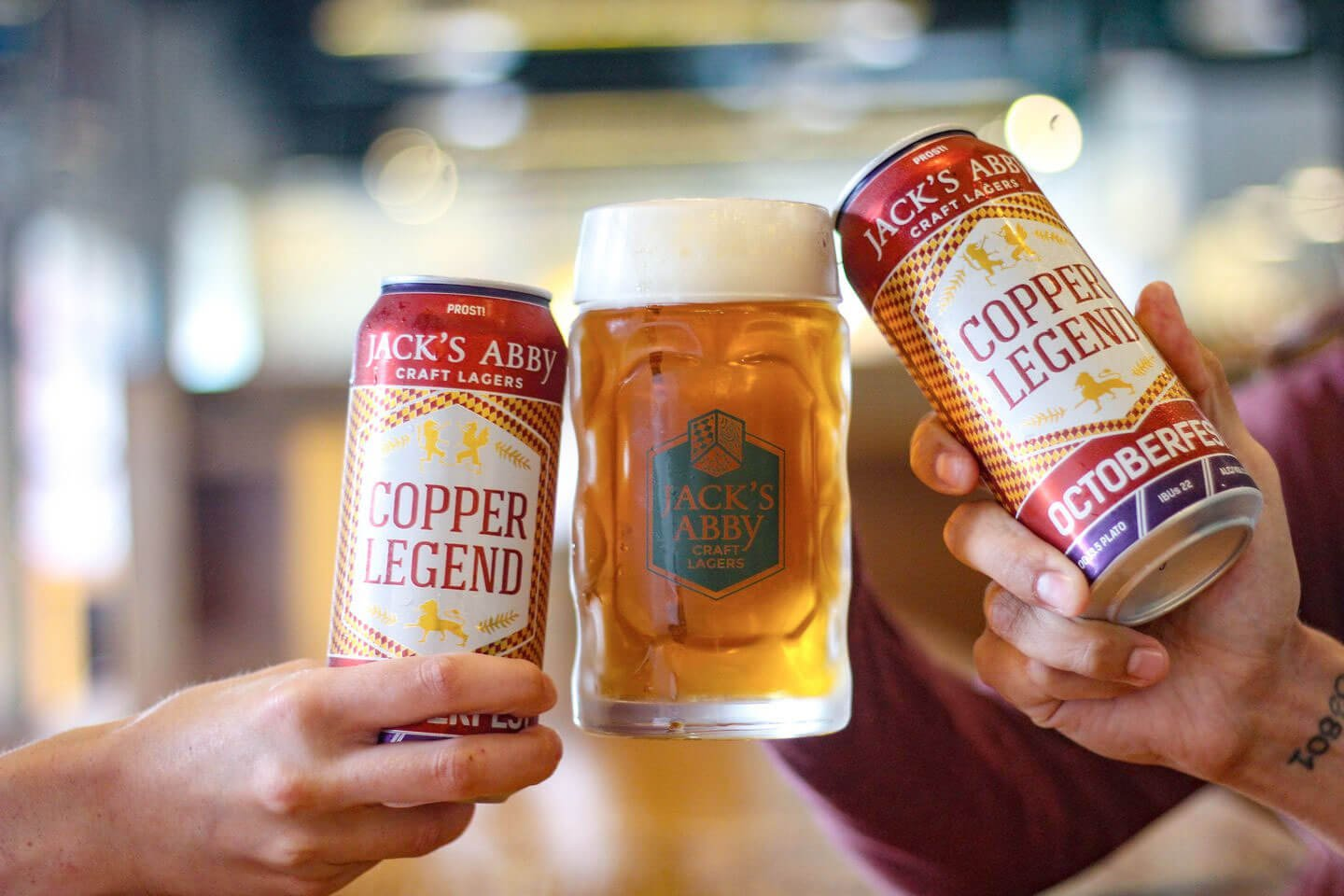A trio of men toast with Copper Legend Oktoberfest beers by Jack's Abby Craft Lagers