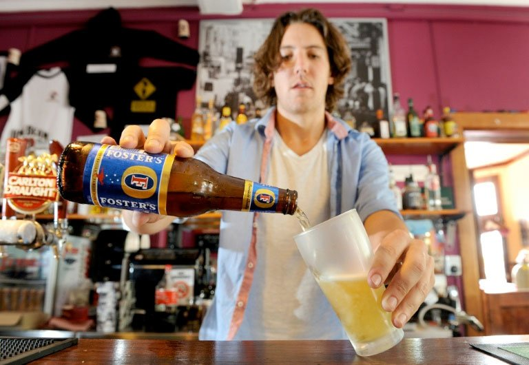 A bartender pours a beer from a bottle of Foster's at a pub in Australia