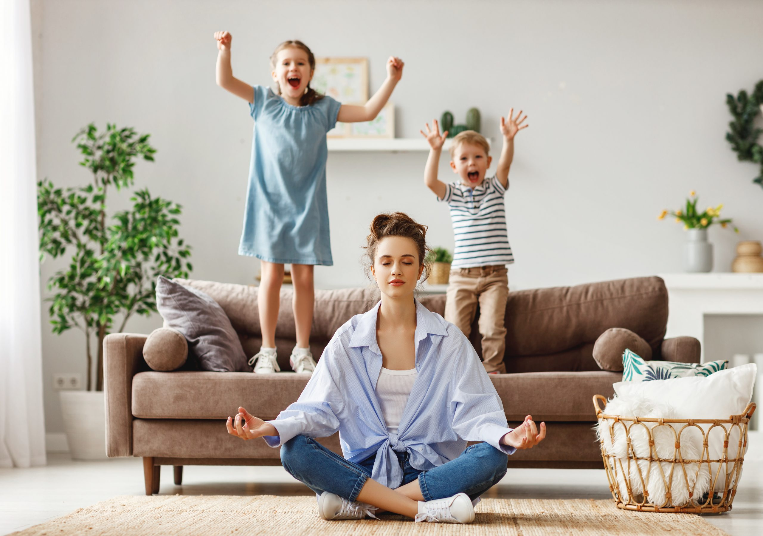 Tranquil young mother practicing yoga to stay calm with mischievous kids at home absolutely adell