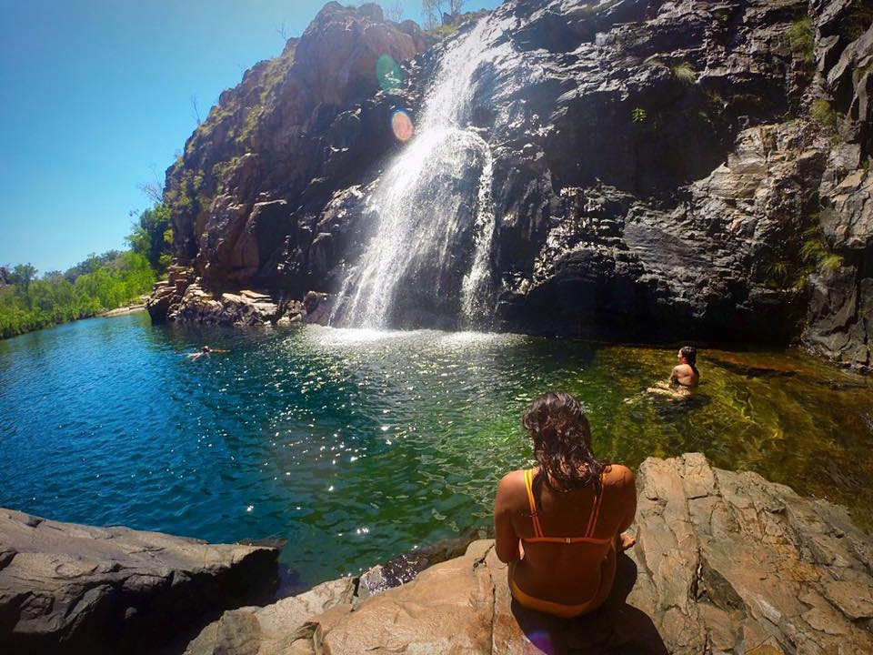 travelling by yourself, girl in yellow bikini sitting on rock at waterfall, kakadu national park, australia, northern territory