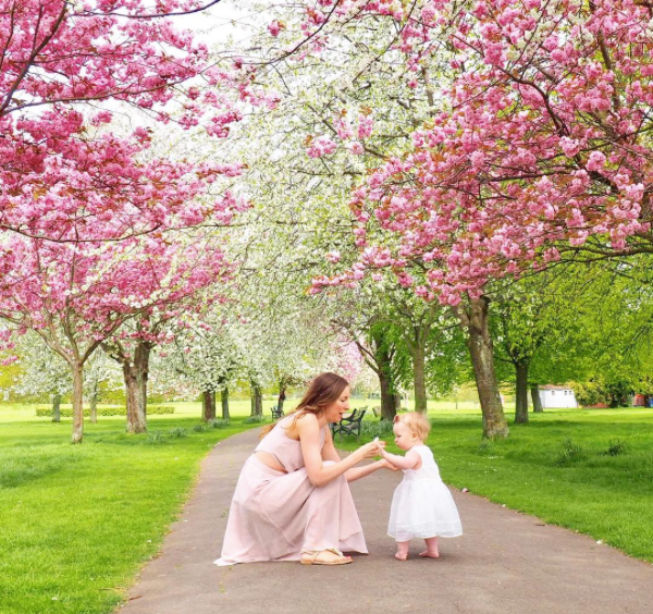 Ayla, Mama Ayla's Adventures, Ayla and her daughter Evie both wearing pink/white dresses in front of pink blossom trees