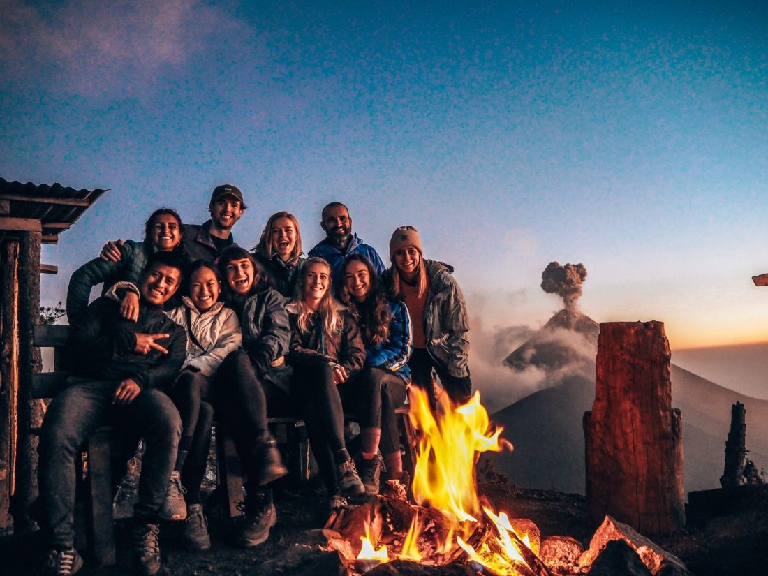 Group at base camp by the fire overlooking volcano