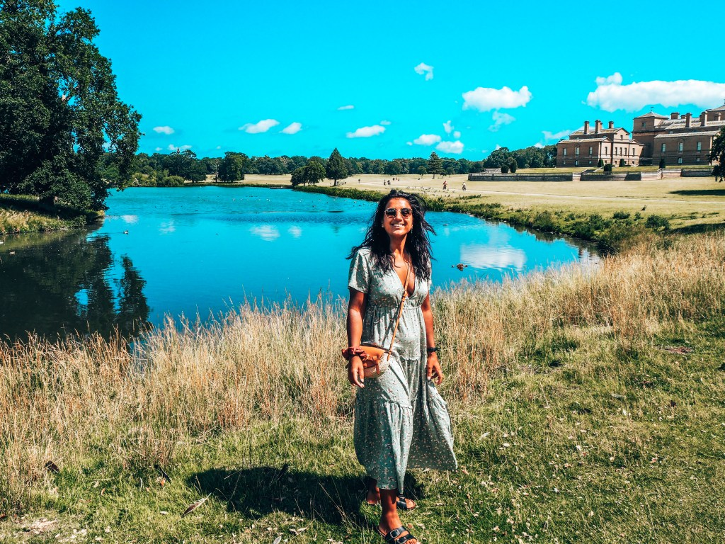 Girl in green dress stood in front of lake at Holkham Hall, North Norfolk, Norfolk stately homes and country houses