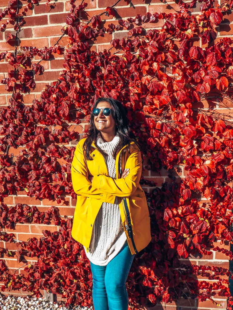 Lucy in yellow raincoat, yellow waterproof jacket, trespass, in front of wall covered in red leaves