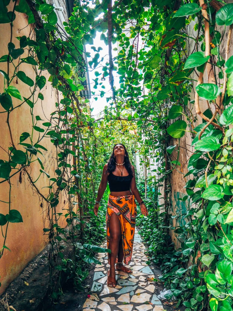 sexual harassment. Lucy in yellow skirt, black top, in alleyway filled with greenery, jungle vibes, guatemala