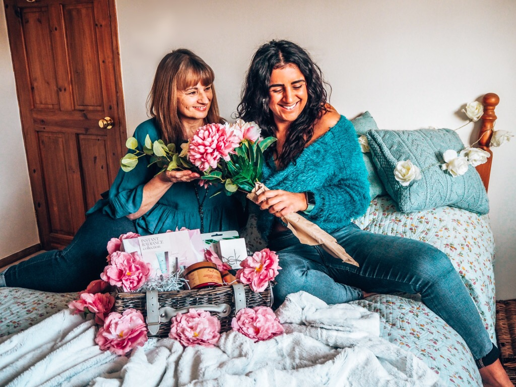 Mother's Day, Absolutely Lucy and her mum in matching green jumpers and jeans on bed with flowers and mother's day gifts of love hamper. Mother's Day Gifts guide